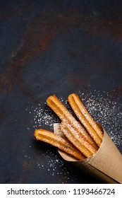 Churros sticks fresh hot in paper bag on dark background top view with copy space