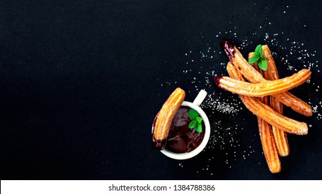 Churros with sugar and chocolate sauce on a black background. Churro - traditional Spanish dessert. Copy Space, top view