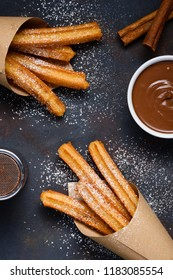 Churros with sugar powder chocolate sauce dip and cinnamon sticks on dark background flat lay top view