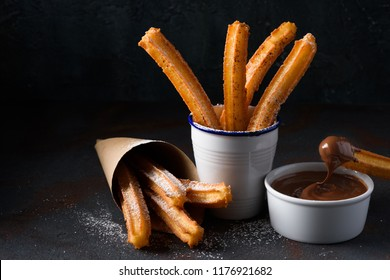 Churros with sugar powder and cinnamon in melted chocolate dip