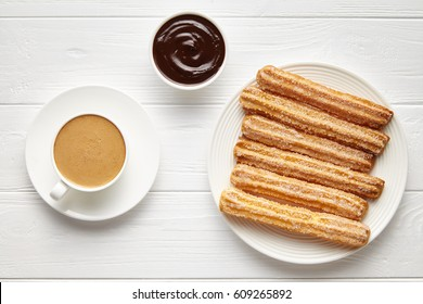 Churros traditional homemade Spain street fast food baked sweet dough snack with chocolate and coffee, white plate, white table background. Flat lay top view