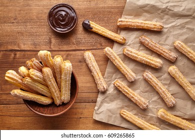 Churros traditional Spain culture breakfast or lunch sweet dough dessert baked pastry street fast food snack with chocolate dipping on rustic wooden table background. Flat lay top view