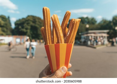 Churros waffles in hand on the street. Churros street food dessert made from dough and sugar. Fast food sweets