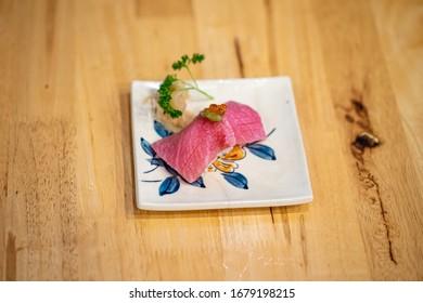 Chutoro, Otoro, Salmon, Sea bass sushi in white plate on Wooden table background
