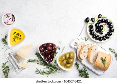 Ciabatta bread, olives, cheese, oil, herbs and spices on white background. Mediterranean snacks. Top view. Copy space