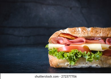 Ciabatta bread stuffed with cheese,meat and vegetables on dark background,selective focus and blank space