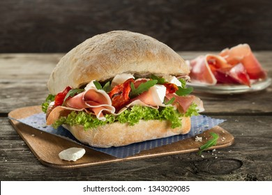 Ciabatta burger sandwich with proscuito ham, mozzarella and salad close up on the wooden background