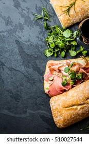 Ciabatta sandwich with jamon ham serrano paleta iberica, arugula, rosemary on stone slate black background. Top view