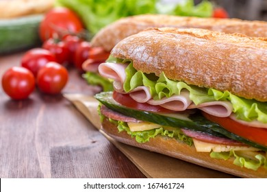 Ciabatta Sandwich with lettuce, slices of fresh tomatoes, cucumber, ham, salami and cheese