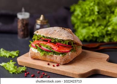Ciabatta sandwich on dark background, selective focus