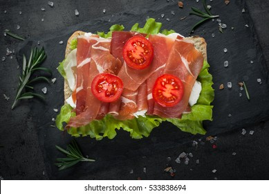 Ciabatta sandwich with  salad leaves jamon serrano and mozzarella cheese over stone background. Top view with copy space
