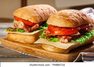Ciabatta sandwich with smoked bacon, cheese and tomato on a cutting board