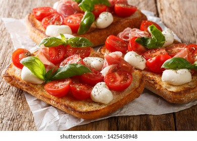 Ciabatta sandwiches with mozzarella, tomatoes, ham and basil close-up on the table. horizontal