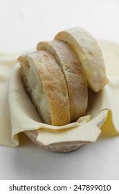 Ciabatta slices over fresh dough in a wooden bowl