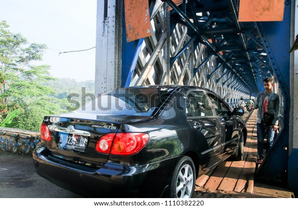 Ciamis, West Java / Indonesia -  March 13, 2016 : A Sedan Entering Cirahong Bridge, A Double Deck Structure of Metal Railway Bridge and Car Bridge Underneath Made by Dutch Colonial