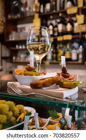 Cicchetti and wine in a venetian cicchetteria. The traditional snacks are similar to tapas, and served in bars and cafes across Venice. They are often eaten standing at the bar.
