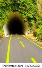 Ciclovia Alpe Adria Radweg bike lane enetering one of the many tunnels on the route, Canal del Ferro valley, Udine, Friuli Venezia-Giulia, Italy