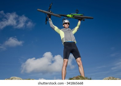 ciclyst raising the mountain bike above his head happy with success
