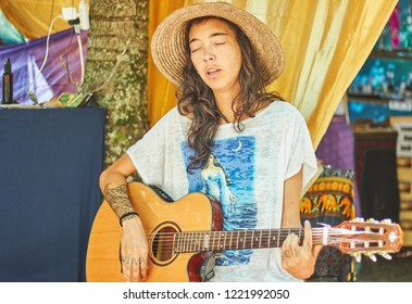 Cidade dos canyons, RS / Brazil - March 2018 : Unidentified woman singing and playing guitar, feeling the music at a alternative trance festival.