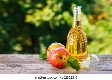 cider vinegar in glass decanter and ripe fresh apples on wooden table with blurred natural background