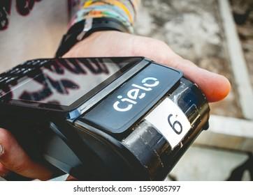 Cielo. Man holding Cielo company credit and debit card machine. Brasilia, Federal District - Brazil. November, 13,  2019.