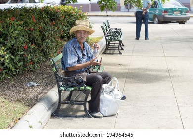 CIENFUEGOS, CUBA - MAY 7, 2014: Old man with straw sobrero seated on a bench in the square of Cienfuegos, Cuba