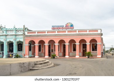 Cienfuegos, Cuba-January 24, 2019:   Restaurant Colonial facade. The old building is located in the central park of the Palmira town. The walls are painted in pink. The sky is overcast