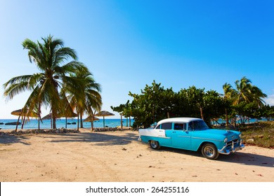 CIENFUEGOS - FEBRUARY 23: Streets of Cienfuegos with classic old car and palm tree in background on February 23, 2015 in Cienfuegos. Old American cars are iconic sight of Cuba street.