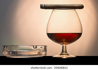 cigar and cognac with ashtray on a black shelf background blur orange in the middle