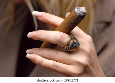 cigar in hands of the woman