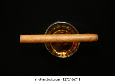 Cigar. Luxury Cuban Cigar with Aged Whisky on black velvet background. Room for text.
