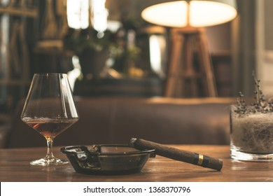 Cigar on a table with whiskey on a side, cigar room representation.