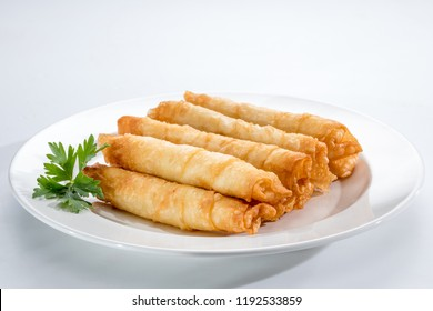 Cigar Pastries on a white plate and background.