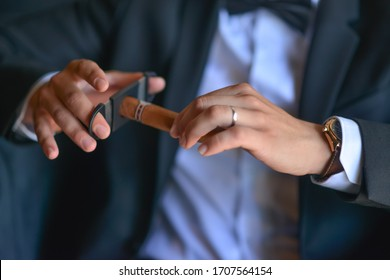 Cigar pruning. Cigar on hands close-up, dressing, man's style, stylish man. Elegant young handsome man. Men's jacket, hand cover the button. Business style.