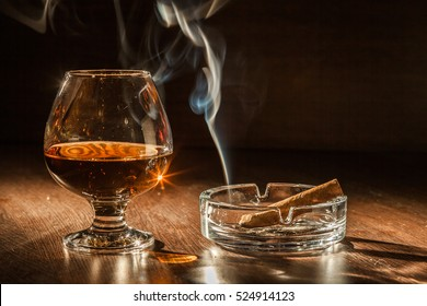 Cigar Smoking in the ashtray, cognac drinks on black background