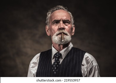 Cigar smoking characteristic senior business man with gray hair and beard wearing blue striped gilet and tie. Against brown wall.