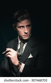 Cigar smoking retro 40s businessman in suit and tie. Hair combed back. Against dark background.