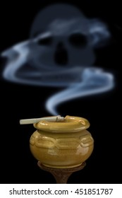 Cigarette in ashtray brown with  of  smoke danger on black background.