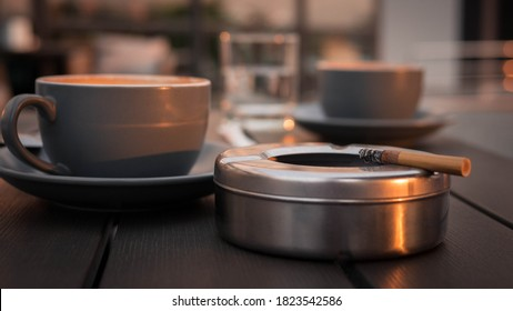 A cigarette with an ashtray and a cup of cappuccino,black coffee with a cigarette,a tobacco product in an ashtray on a wooden table in a cafe.