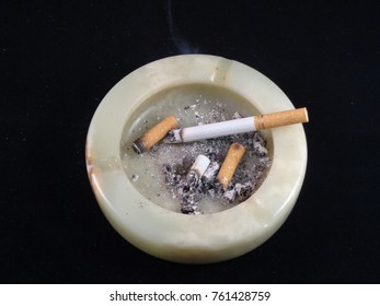 cigarette and ashtray isolated on a black background