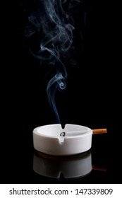 Cigarette in an ashtray on a black background