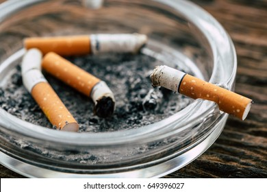 cigarette with ashtray on wooden background