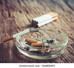 cigarette with ashtray on wooden table ,vintage filter