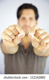 Cigarette being broken in two pieces by man stop smoking stop addiction