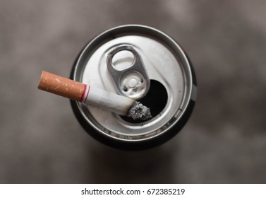 cigarette burning on can