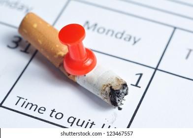 Cigarette butt impaled on calendar