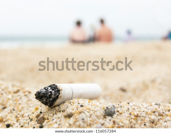 Cigarette butt on a beach, pollution concept