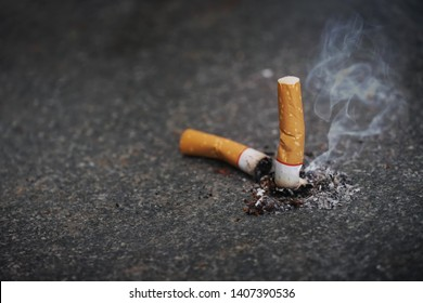 cigarette butt on black granite floor. 31 May World No Tobacco Day Tobacco and lung health concept .