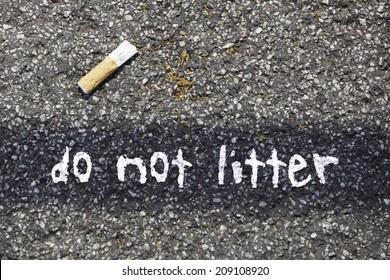 cigarette butt on a tar road with the written massage: do not litter