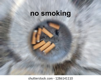 cigarette butts in ashtray - no smoking